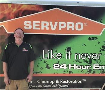 Photo of SERVPRO of Spencer & Iowa Great Lakes Production Crew Member Mike Pomeroy standing next to company trailer.