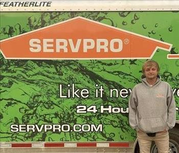 Photo of male SERVPRO of Spencer & Iowa Great Lakes Production Crew Member Tanner Wallace standing next to company trailer.