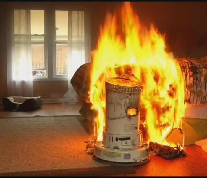 Photo of a space heater engulfed in flames.